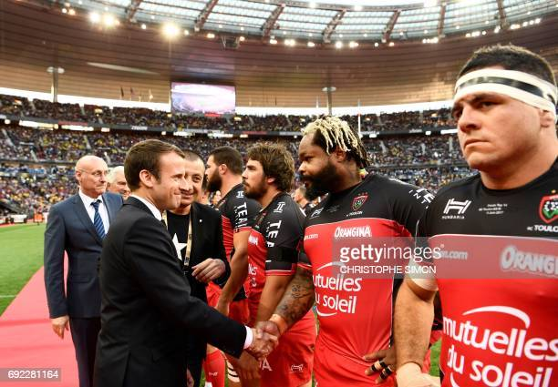 French president Emmanuel Macron flanked by French rugby union federation president Bernard Laporte and Mourad Boudjellal shakes hands with Toulon's...