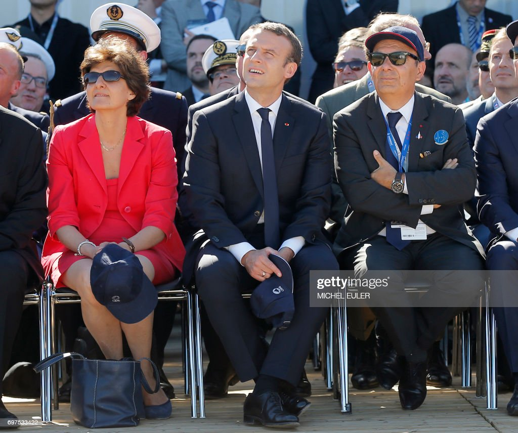 French President Emmanuel Macron (C) French defense minister Sylvie Goulard (L) and Dassault Aviation CEO Eric Trappier watch demonstration flights as part of the Paris Air Show in Le Bourget, north of Paris, on June 19, 2017. Macron landed on June 19 at the Bourget airfield in an Airbus A400-M military transport plane to launch the aviation showcase, where the latest Boeing and Airbus passenger jets will vie for attention with a F-35 warplane, drones and other and high-tech hardware. / AFP PHOTO / POOL / Michel Euler