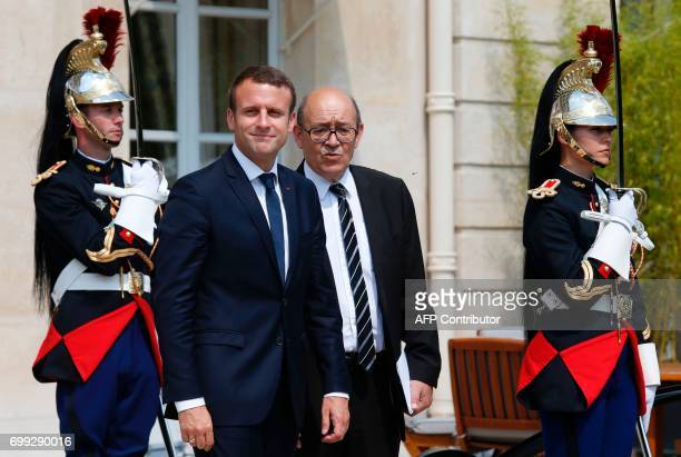 French President Emmanuel Macron gestures as he speaks with French Foreign Minister JeanYves Le Drian after meetings with The Crown Prince of Abu...