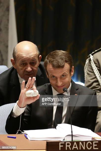 French President Emmanuel Macron gestures as he speaks with French Foreign Minister JeanYves Le Drian as he participates in an open debate of the...