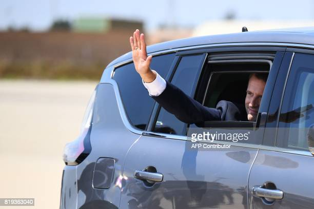 French President Emmanuel Macron gestures from a car as he leaves after visiting French air force base BA 125 in Istres southeastern France on July...