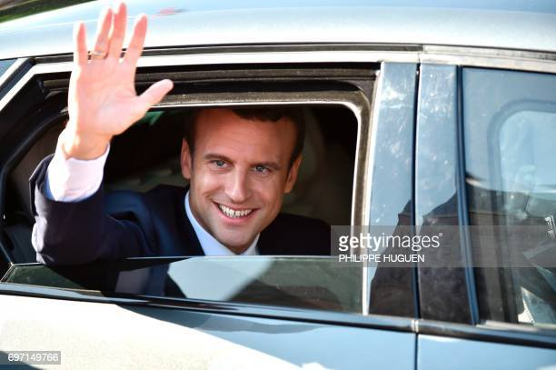 French President Emmanuel Macron gestures from his car as he leaves to vote in Le Touquet northern France during the second round of the French...