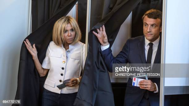 French President Emmanuel Macron gestures next to his wife Brigitte Macron as they exit voting booths at a polling station during the first round of...