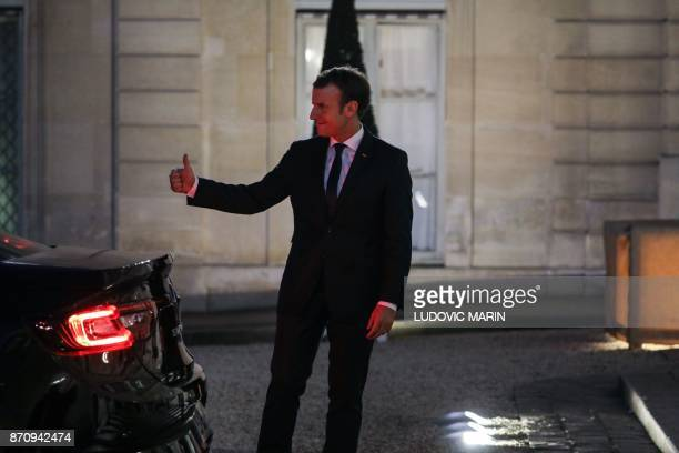 French President Emmanuel Macron gives a thumb up after escorting his Cypriot counterpart following their meeting at the Elysee palace on November 6...