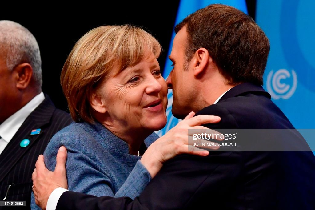 French President Emmanuel Macron (R) greets German Chancellor Angela Merkel before her speech at the UN conference on climate change (COP23) on November 15, 2017 in Bonn, western Germany. / AFP PHOTO / John MACDOUGALL