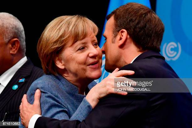 French President Emmanuel Macron greets German Chancellor Angela Merkel before her speech at the UN conference on climate change on November 15 2017...
