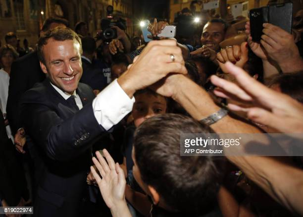 French President Emmanuel Macron greets people during his visit to the 'Rencontres d'Arles' annual photography festival in Arles southern France on...