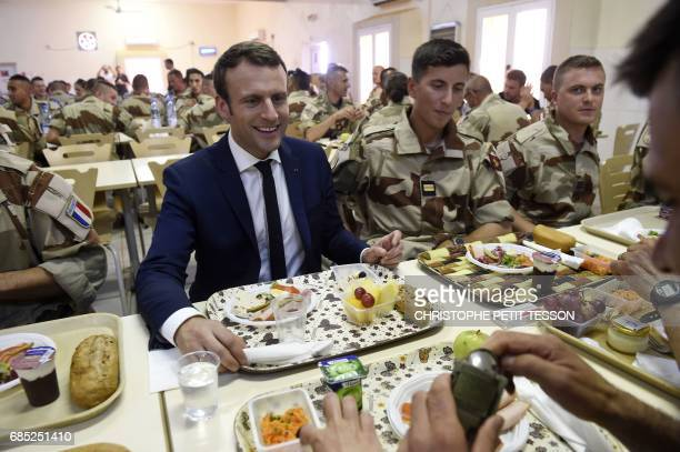 TOPSHOT French President Emmanuel Macron has a lunch break with French troops during his visit to France's Barkhane counterterrorism operation in...