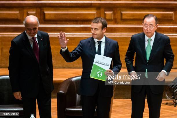 French President Emmanuel Macron holding a copy of the World Environment Pact gestures after he delivered a speech as former French Foreign Minister...