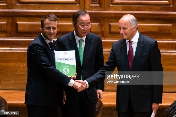 French President Emmanuel Macron holding a copy of the World Environment Pact shakes hand with former French Foreign Minister Laurent Fabius as...