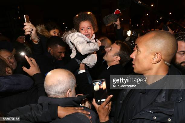 French President Emmanuel Macron holds a screaming baby during a visit focused on the theme of urbanplanning in ClichysousBois northern Paris on...