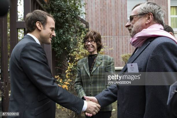 French President Emmanuel Macron is greeted by President of French charitable organisation 'Les Restos du Coeur' Patrice Blanc and widow of French...