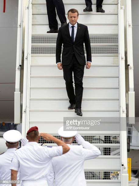French President Emmanuel Macron is greeted upon arrival at the start of his visit at the Felix Eboue Airport of Cayenne in French Guiana on October...