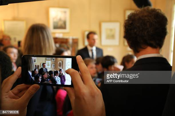 French President Emmanuel Macron is seen through a cellular telephone as he speaks with schoolchildren watched by French Minister of Culture...
