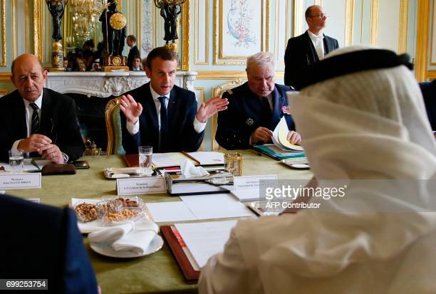French President Emmanuel Macron is watched by French Foreign Minister JeanYves Le Drian as he speaks with Abu Dhabi's Crown Prince Sheikh Mohammed...