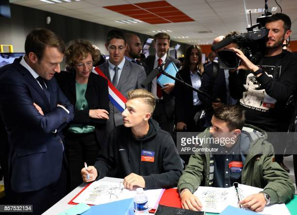 French President Emmanuel Macron is watched by Minister of Employment Muriel Penicaud as he speaks with students in a civil engineering class during...