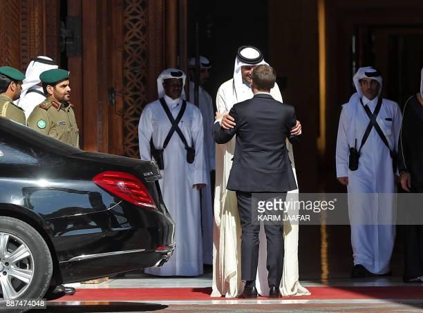 French President Emmanuel Macron is welcomed by Qatari Emir Sheikh Tamim bin Hamad alThani at the Qatari capital Doha on December 7 2017 / AFP PHOTO...