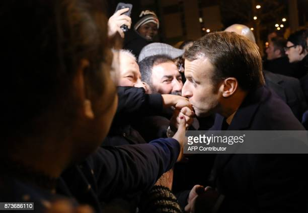 French President Emmanuel Macron kisses a hand of a resident during a visit focused on the theme of urbanplanning in ClichysousBois northern Paris on...