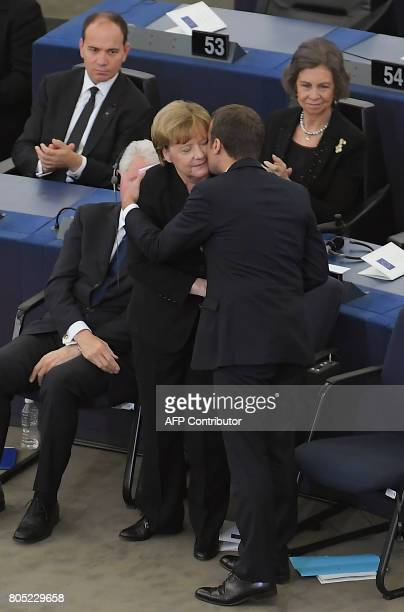 French President Emmanuel Macron kisses German Chancellor Angela Merkel after he delivered a speech during a ceremony for late German Chancellor...