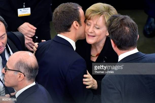 French President Emmanuel Macron kisses German Chancellor Angela Merkel before the beginning of the memorial ceremony for former German Chancellor...