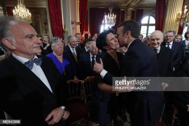 TOPSHOT French President Emmanuel Macron kisses his mother Francoise Nogues as his father JeanMichel Macron looks on during the handover ceremony...