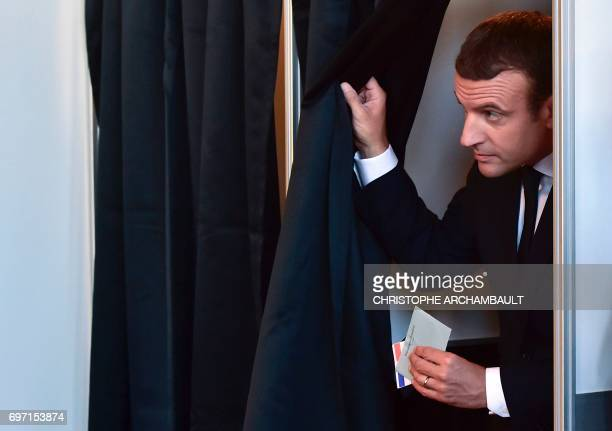French President Emmanuel Macron leaves a polling booth with his ballot as he votes at a polling station in Le Touquet northern France during the...