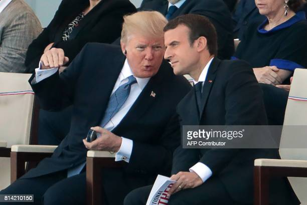French President Emmanuel Macron listens to US President Donald Trump as they attend the annual Bastille Day military parade on the ChampsElysees...