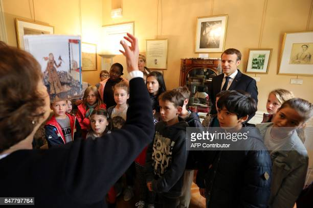French President Emmanuel Macron listens with schoolchildren as a guide speaks during a visit to The Château de MonteCristo at MarlyleRoi on...