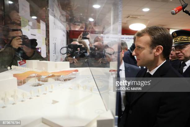 French President Emmanuel Macron looks at a model during a visit at Dhuys social centre in ClichysousBois northern Paris on November 13 as part of a...