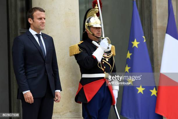 French President Emmanuel Macron looks on after escorting his Madagascar counterpart as he leaves following their meeting at the Elysee palace on...