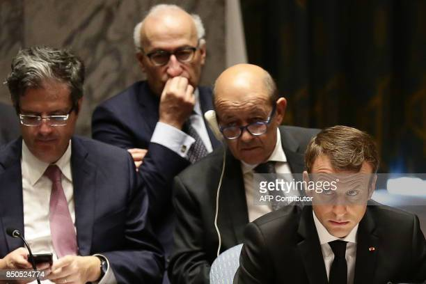 French President Emmanuel Macron looks on with French Foreign Minister JeanYves Le Drian as he participates in an open debate of the United Nations...
