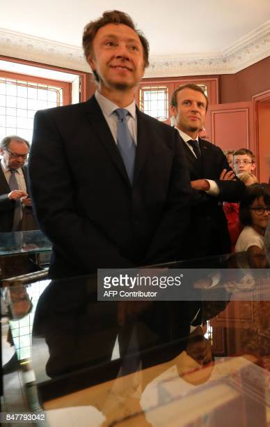 French President Emmanuel Macron looks on with schoolchildren and television host Stéphane Bern as he stands beside a display during a visit to The...
