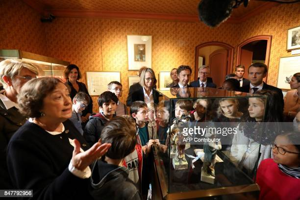 French President Emmanuel Macron looks on with schoolchildren French Minister of Culture Francoise Nyssen and television host Stéphane Bern as he...