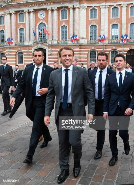 French President Emmanuel Macron walks surrounded by members of the presidential security service at the Place du Capitole in Toulouse southern...
