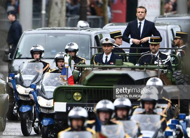TOPSHOT French President Emmanuel Macron parades in a car on the Champs Elysees avenue after his formal inauguration ceremony as French President on...
