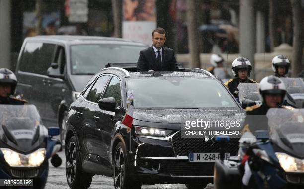 French President Emmanuel Macron parades under the rain in a Citroen DS car on the Champs Elysees avenue after his formal inauguration ceremony as...