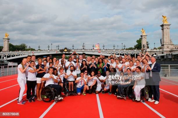 French President Emmanuel Macron Paris city mayor Anne Hidalgo and French Sports Minister Laura Flessel pose with French athletes on athletics tracks...