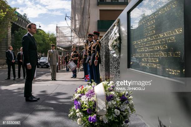 French President Emmanuel Macron pays his respects after laying a wreath at the Vel d'Hiv Roundup memorial in Paris on July 16 during a ceremony...