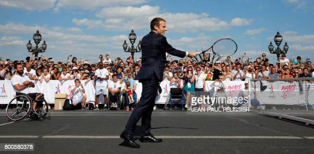 French President Emmanuel Macron plays tennis with French wheelchair tennis player Michael Jeremiasz during a visit to a site near the Invalides in...