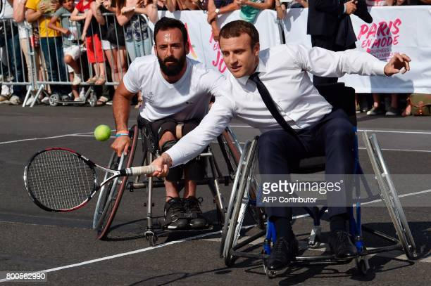 French President Emmanuel Macron plays wheelchair tennis with French wheelchair tennis player Michael Jeremiasz during a visit to a site near the...