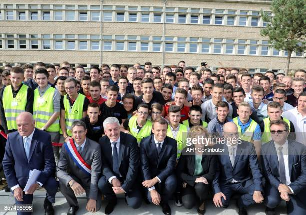 French President Emmanuel Macron poses alongside Minister of Employment Muriel Penicaud and Minister of Education JeanMichel Blanquer and students...