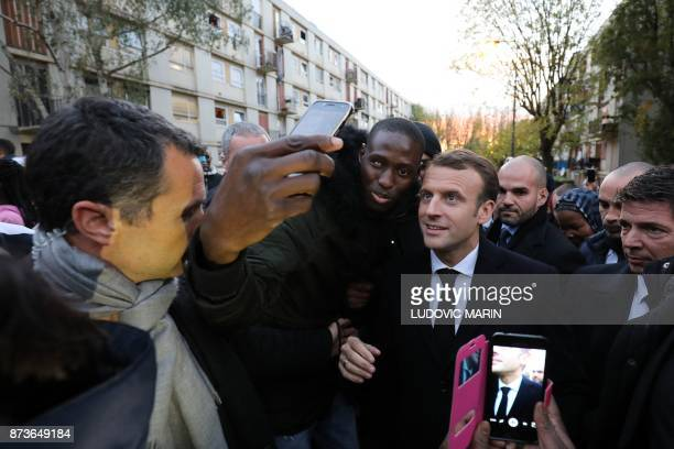 French President Emmanuel Macron poses for a selfie picture as he meets residents of the Cite du Chene Pointu during his visit focused on the theme...