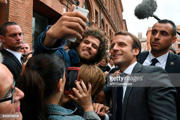 French President Emmanuel Macron poses for a selfie with people at the Place du Capitole in Toulouse southern France before attending the round table...