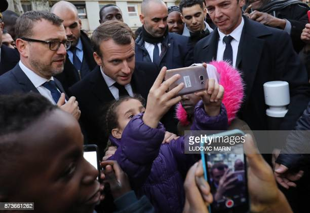 French President Emmanuel Macron poses for a selifie picture with a child as he meets residents of the Cite du Chene Pointu during his visit focused...