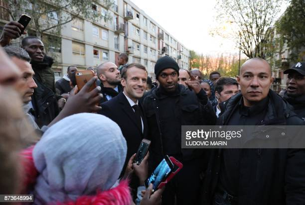 French President Emmanuel Macron poses for pictures as he meets residents of the Cite du Chene Pointu during his visit focused on the theme of...