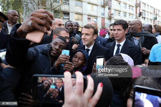 French President Emmanuel Macron poses for selfie pictures as he meets residents of the Cite du Chene Pointu during his visit focused on the theme of...