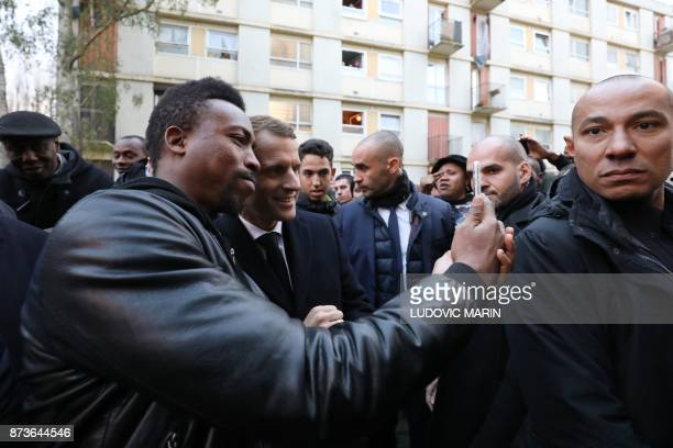 French President Emmanuel Macron poses with a man for a selfie picture taken with a mobile phone as he arrives at the Cite du Chene pointu during his...
