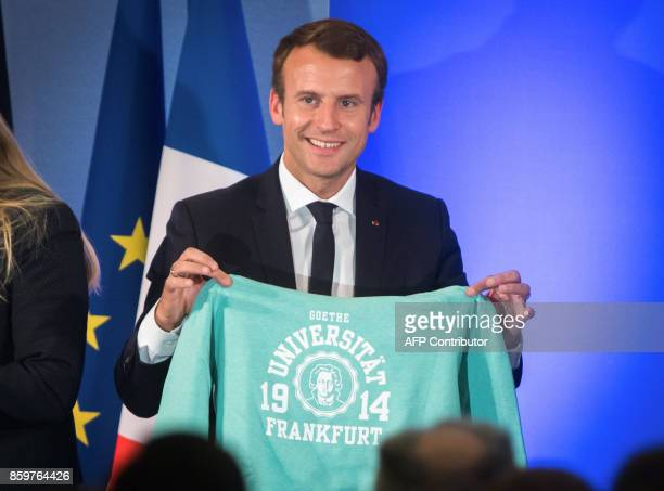 French President Emmanuel Macron poses with a sweatshirt with the logo of the Goethe University in Frankfurt after an open debate on Europe on...