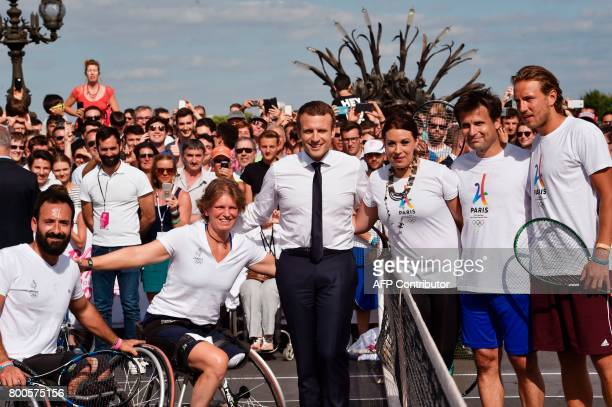 French President Emmanuel Macron poses with former French tennis player Fabrice Santoro French wheelchair tennis player Michael Jeremiasz and...