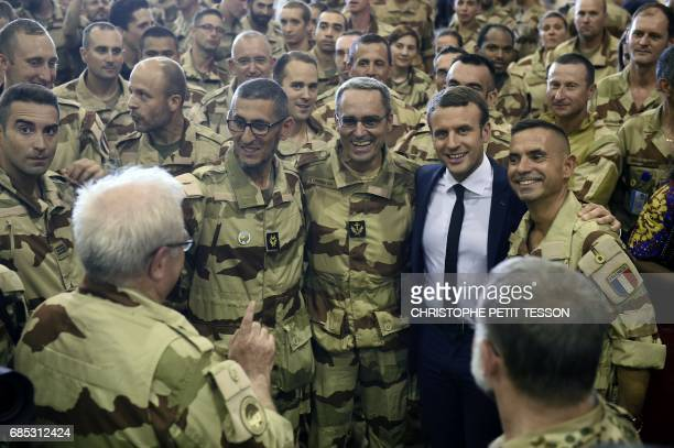 TOPSHOT French President Emmanuel Macron poses with French troops during his visit to the France's Barkhane counterterrorism operation in Africa's...